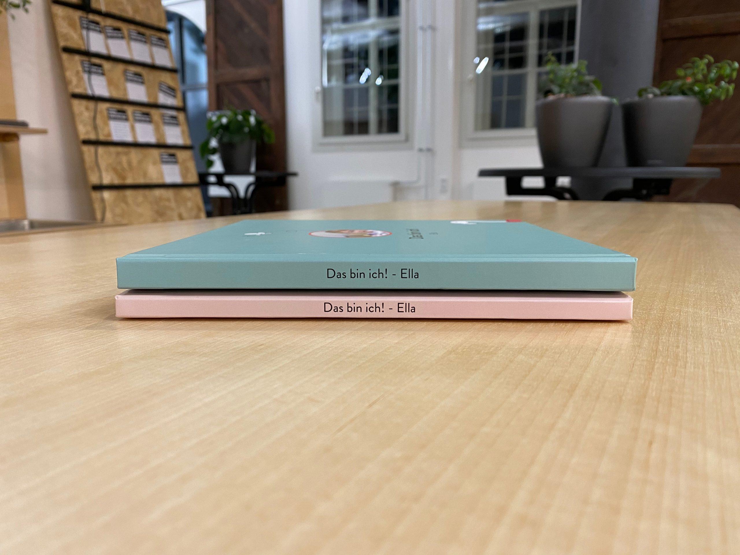 Buchstapel aus Babytagebüchern in blau und rosa.