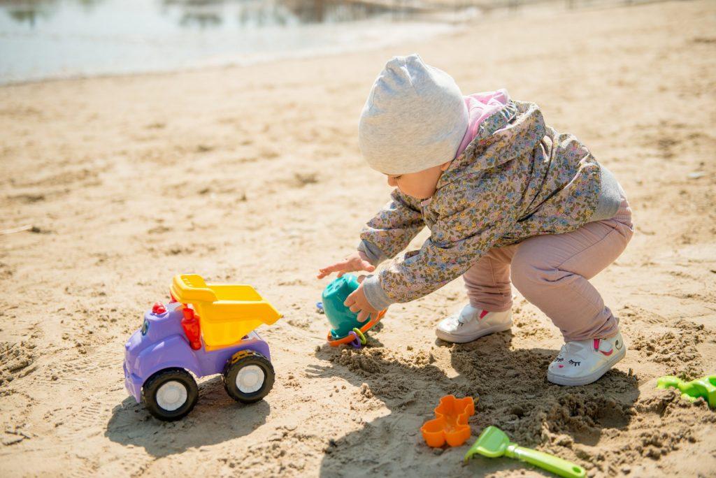 Baby spielt im Sand